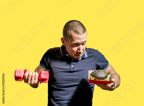 A man holds a black Burger in one hand and a dumbbell in the other #359204316