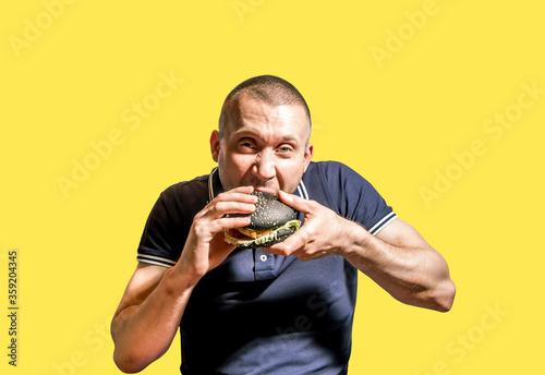 A hungry Man enjoys eating a black Burger . #359204345