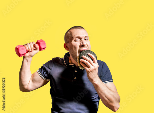 A hungry Man enjoys eating a black Burger and holding a dumbbell . #359204372