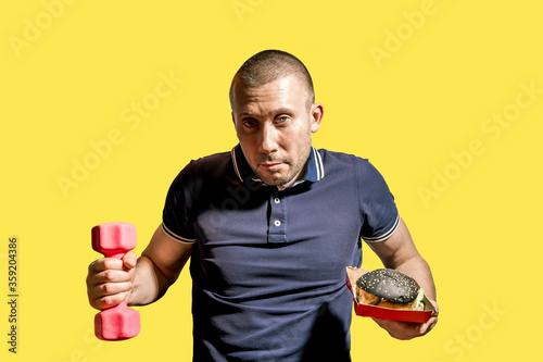 a man holds a black burger in one hand and a dumbbell in the other #359204386