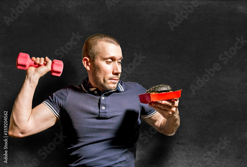 A man holds a black Burger in one hand and a dumbbell in the other #359204562