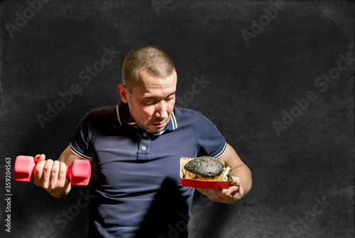A man holds a black Burger in one hand and a dumbbell in the other #359204563