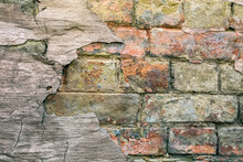 Old Brick Wall With Remnants Of Concrete Plaster. Background Texture