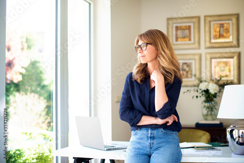 Obraz Attractive smiling mature woman standing at desk and thinking - fototapety do salonu