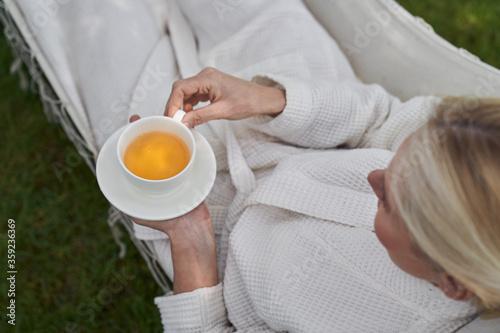 Obraz Woman in hammock relaxing with cup of tea - fototapety do salonu