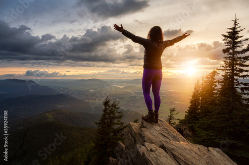 Adventurous Girl on top of a Rocky Mountain overlooking the beautiful Canadian Nature Landscape during a dramatic Sunset Fototapet