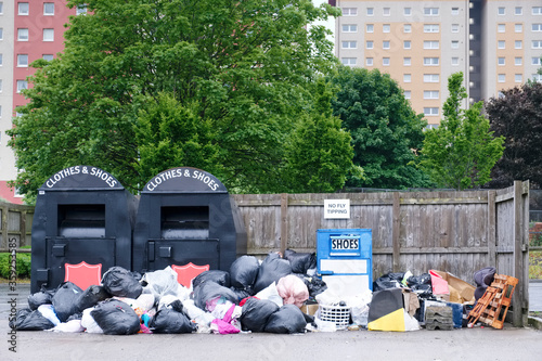 Fototapety, obrazy: Clothes and shoes charity recycle container and black bin bags in a group dump in. council estate
