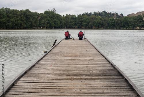 Two men fishing on a pier in Lake Evans in Fairmount park in Riverside Californi Fotobehang