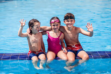 Kids Playing In The Swimming Pool. Childhood, Summer And Vacation Concept