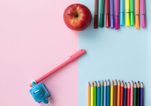 Colored Pencils, Felt-tip Pens And Toy Robot With A Pen On Light Blue  And Rose Background. Back To School Flatlay, Top View.