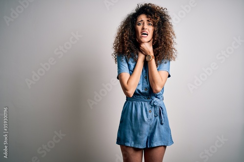 Photo Young beautiful woman with curly hair and piercing wearing casual denim dress shouting and suffocate because painful strangle