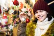 canvas print picture - girl choosing Christmas decoration at market