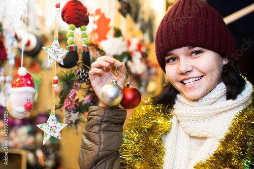 Photo girl choosing Christmas decoration at market