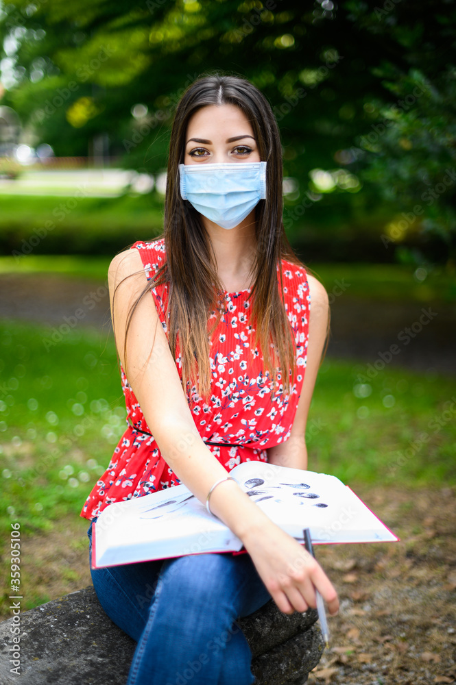 Fototapeta Beautiful female college student reading a book on a bench in a park and wearing a mask in coronavirus times