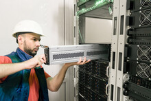 An Engineer Installs A New Battery Pack Into An Uninterruptible Power Supply. Replacing The Power Module In The Server Room Rack. Maintenance Of Data Center Equipment.
