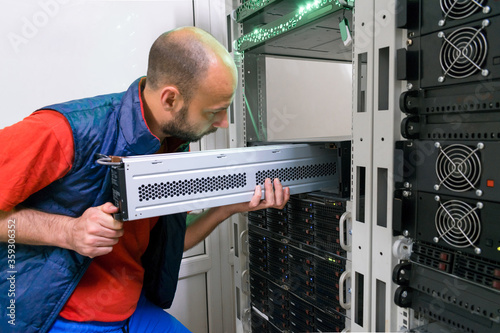 Fotomural The man installs a new battery into the uninterruptible power supply