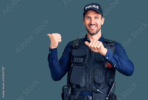 Obraz na płótnie Young handsome man wearing police uniform pointing to the back behind with hand