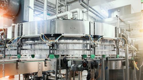 Fotografiet Industrial machine conveyor with plastic bottles in beverage factory, industry equipment