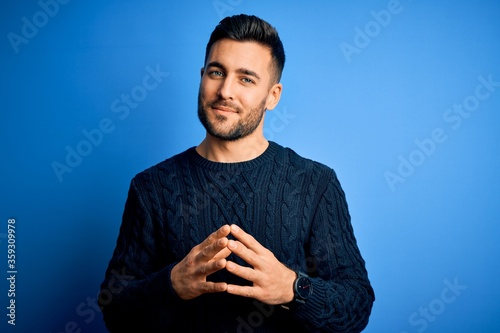Fotografie, Obraz Young handsome man wearing casual sweater standing over isolated blue background Hands together and fingers crossed smiling relaxed and cheerful