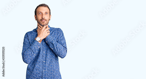 Photo Young handsome man wearing casual clothes shouting and suffocate because painful strangle