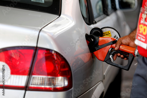 Fototapeta salvador, bahia / brazil - august 20, 2019: gas station attendant is seen fueling a vehicle at a gas station in the city of Salvador