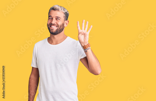 Obraz na plátně Young handsome blond man wearing casual t-shirt showing and pointing up with fingers number four while smiling confident and happy
