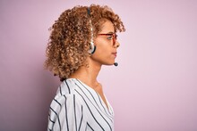 African American Curly Call Center Agent Woman Working Using Headset Over Pink Background Looking To Side, Relax Profile Pose With Natural Face With Confident Smile.
