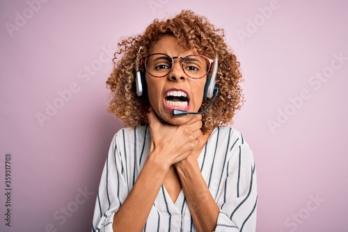 African american curly call center agent woman working using headset over pink background shouting and suffocate because painful strangle Canvas Print