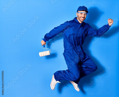 Leinwand Poster Young handsome hispanic man wearing painter uniform and cap smiling happy
