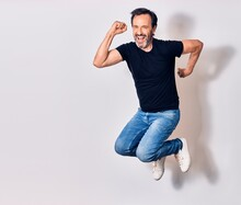 Middle Age Handsome Man Wearing Casual Clothes Smiling Happy. Jumping With Smile On Face Doing Winner Gesture With Fists Up Over Isolated White Background