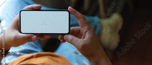 Male freelancer resting with horizontal mock-up smartphone while lying relaxed on office chair