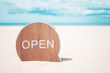 Now Open Sign Board Stand On Sand Summer Beach Background Metaphor To Time To Travel Relax Tourism Season With Copyspace.