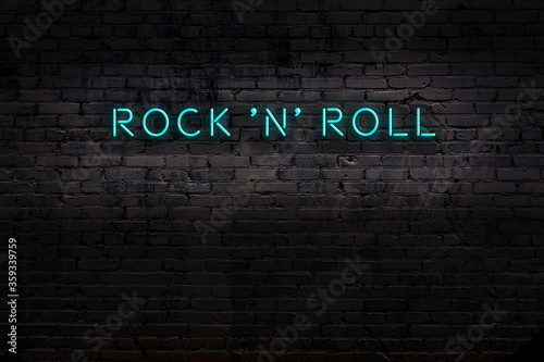 Fotomural Neon sign. Word rock 'n' roll against brick wall. Night view