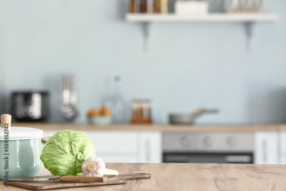 Fototapeta Fresh vegetables with pot and cutting board on kitchen table