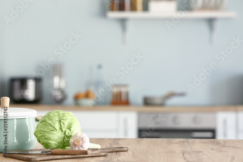 Fresh vegetables with pot and cutting board on kitchen table Fototapet