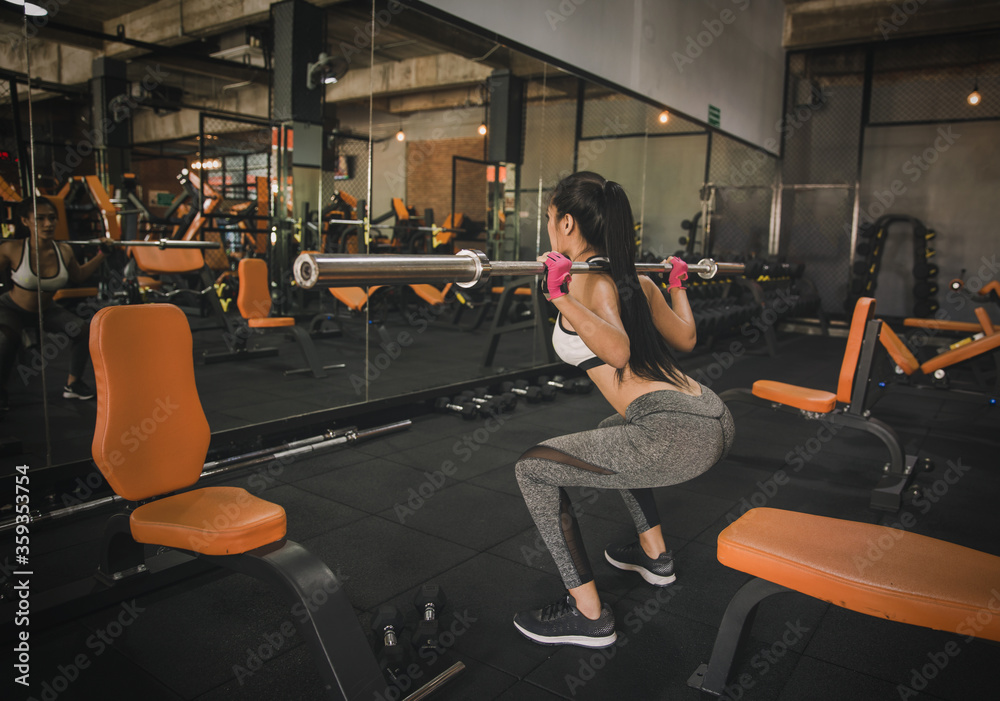 Fototapeta Young woman is working out at gym in light modern gym.