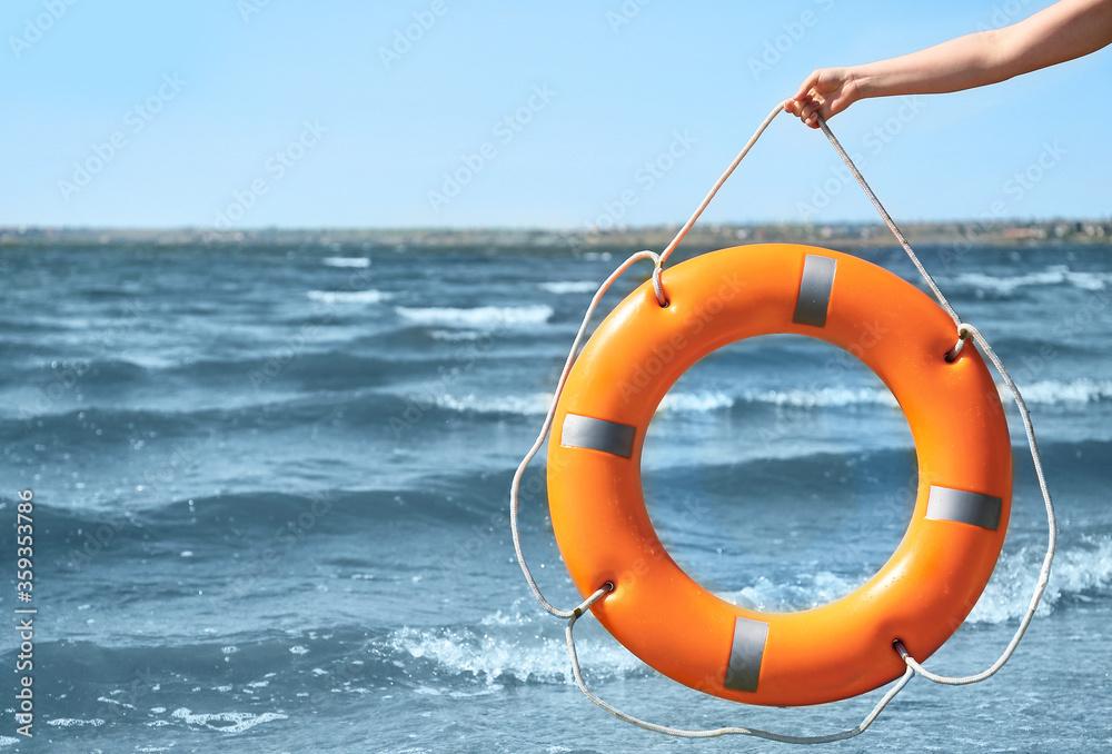 Fototapeta Woman with lifebuoy ring near river