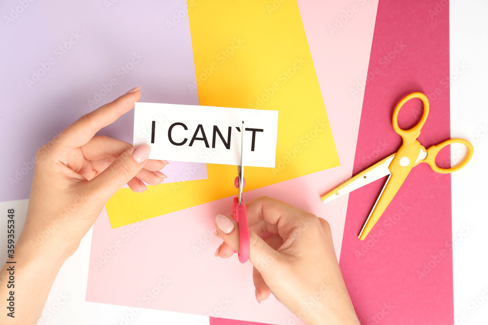 Fototapeta Woman with scissors turning phrase I CAN'T to I CAN on color background