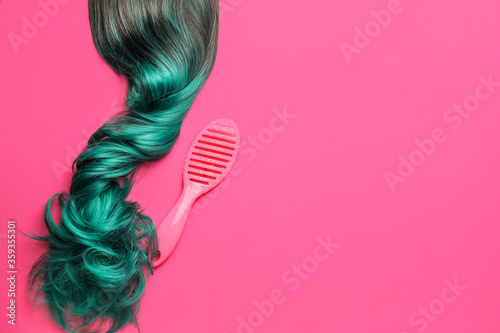 Unusual wig and brush on color background Fotobehang