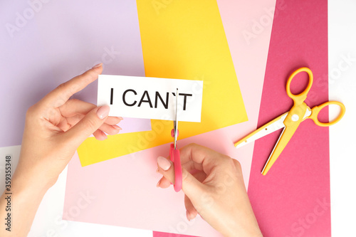 Photo Woman with scissors turning phrase I CAN'T to I CAN on color background
