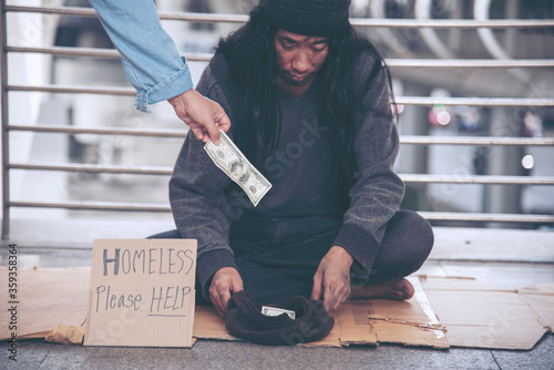 Fotomural Woman helping hands to homeless people poverty beggar man holding hands asking for money job and hoping help in helpless dirty city sitting on streets