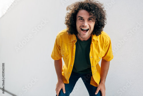 Half-length image of cheerful handsome man with curly hair smiling broadly, posing for social advertisement against white wall in the city street Fototapet