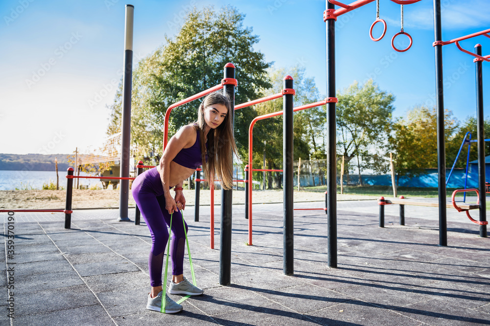 Fototapeta Beautiful  young female doing exercises on the street of the playground. Concept of good physical shape and healthy lifestyle