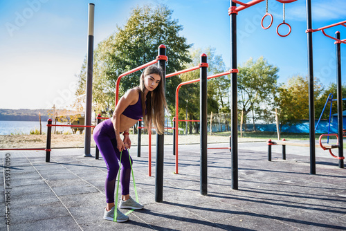 Fototapeta Beautiful  young female doing exercises on the street of the playground. Concept of good physical shape and healthy lifestyle obraz