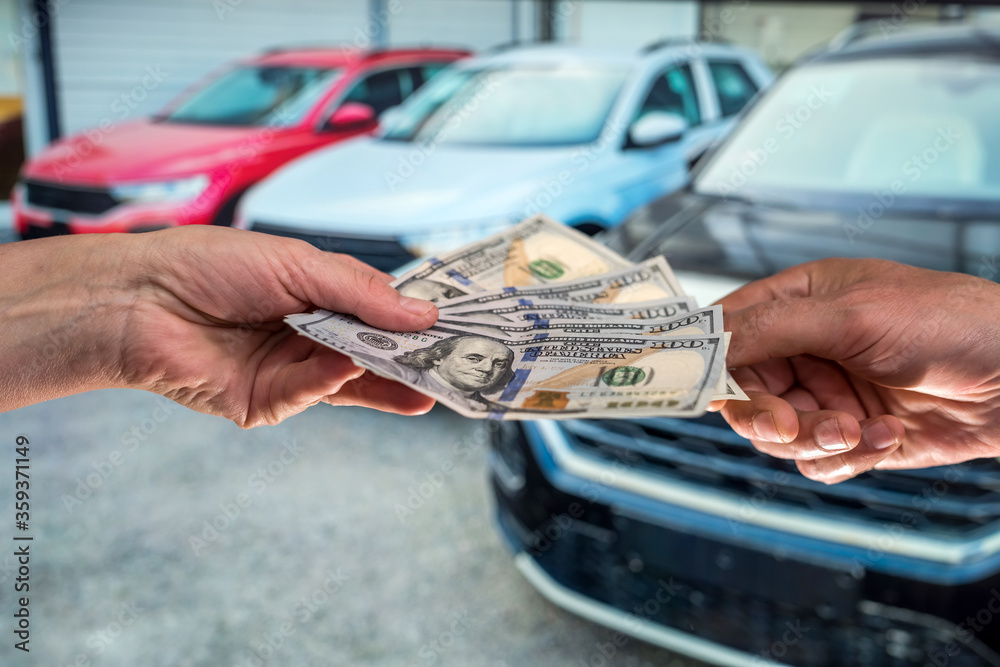 Fototapeta businessman gives money to rent a car for summer vacation