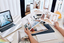 Interior Designer Sitting At Desk And Looking At Printed Photos Of Clients Rooms After Renovation