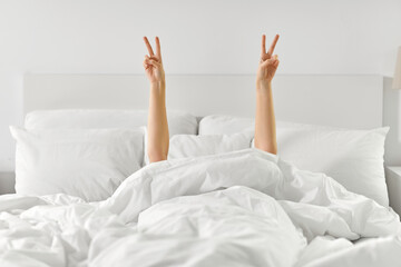 gesture, comfort and morning concept - hands of young woman lying in bed and showing peace hand sign at home bedroom