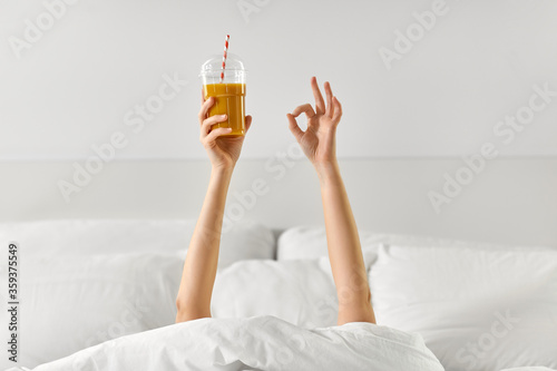 gesture, drink and morning concept - hands of young woman lying in bed with cup Wallpaper Mural