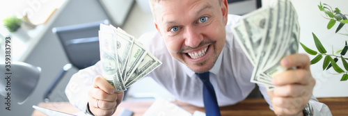 Fototapeta Top view of happy smiling man holding money fans in hands. Cheerful gambler getting big cash prize at online lottery. Joyful guy showing banknotes in office. Game of chance concept obraz