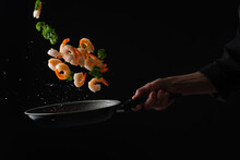 Shrimps With Parsley Frying In A Pan, The Chef Cooks, Freezing In Motion On A Black Background, Healthy And Tasty Food